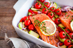 Raw fresh delicious salmon, cherry tomatoes, onion, zucchini, pepper and lemon in pan, ready to cook