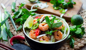 Vietnamese prawn noodle , Tasty traditional  with rice noodles, spring onions, king prawns, bird's eye green, red chilies and shiitake mushrooms. Decorated with piece of fresh lime, leaves of mint, basil and slices of spicy peppers. All in bowl with chopsticks on natural wooden background.