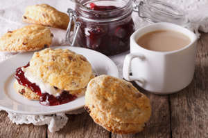 Scones with jam and tea with milk close-up on the table. horizontal