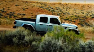 a white car driving down a dirt road: Jeep Gladiator Torture Testing Ad