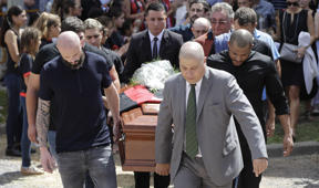 Nantes defender Nicolas Pallois, left, and family and friends of Argentina soccer player Emiliano Sala carry Sala's coffin during his funeral in Progreso, Argentina, Saturday, Feb. 16, 2019. The Argentina-born forward died in an airplane crash in the English Channel last month when flying from Nantes in France to start his new career with English Premier League club Cardiff. (AP Photo/Natacha Pisarenko)