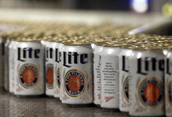 "FILE - In this March 11, 2015 photo, newly-filled and sealed cans of Miller Lite beer move along on a conveyor belt, at the MillerCoors Brewery, in Golden, Colo. Advertising regulators say MillerCoors can claim Miller Lite has ""more taste"" than Bud Light and Michelob Ultra but recommends the brewer stop commercials that make it appear that the conclusion is based on a survey on taste preference. Both sides of the dispute claimed victory Thursday, Dec. 20, 2018, from the National Advertising Division's conclusion, a self-regulatory agency for the advertising industry. (AP Photo/Brennan Linsley, File)"