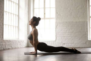 Young attractive woman practicing yoga, stretching in Urdhva mukha shvanasana exercise, upward facing dog pose, working out wearing black sportswear bra and pants, full length, white studio background