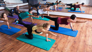 Group of young glad people doing yoga in dance hall. Focus on brunet man