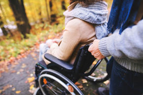 Unrecognizable senior couple on a walk in a beautiful autumn nature. A man and woman in a wheelchair walking in forest.