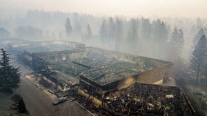 In this Thursday, Nov. 15, 2018 file photo smoke hangs over the scorched remains of Old Town Plaza following the wildfire in Paradise, Calif.