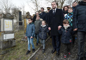 French President Emmanuel Macron (C) holds children by the hands as he walks past graves vandalised with swastikas during a visit at the Jewish cemetery in Quatzenheim, on February 19, 2019, on the day of a nationwide marches against a rise in anti-Semitic attacks. - Around 80 graves have been vandalised at the Jewish cemetery in the village of Quatzenheim, close to the border with Germany in the Alsace region, which were discovered early February 19, 2019, according to a statement from the regional security office.
