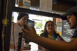WASHINGTON, DC - JULY 5: After pulling out cash to pay for food, customers Aaron Bateman, L, and Roxann Barr (cq), C, hear from cashier Obed Amaya that the restaurant does not accept cash at Surfside, a taco/burrito walk-up only restaurant, on Thursday, July 5, 2018, in Washington, DC.  Bateman and Barr, who are vacationing in DC from Norfolk, VA, found Surfside online and walked half a mile to try the food.  They initially planned to walk with cash only but were glad they brought their debit cards.  As more and more fast-casual restaurants in D.C. and beyond are refusing to accept cash for security and efficiency reasons, some advocates for the poor and lawmakers on the D.C. Council are pushing back. They say cashless policies in places such as Sweet Green, B. Doughnut and Surfside discriminate against homeless people and others who don't have bank accounts. A bill before the D.C. Council would require businesses to accept cash.    (Photo by Jahi Chikwendiu/The Washington Post via Getty Images)