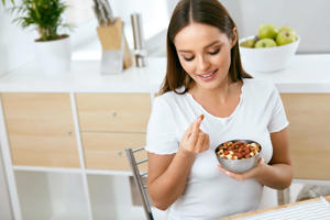 Healthy Food. Happy Woman Eating Nuts Holding Plate In Hands. Portrait Of Beautiful Smiling Female ON Diet With Raw Organic Almonds In Hands In Kitchen. Healthy Fats. High Quality