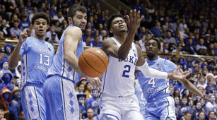 Duke's Cam Reddish (2) struggles for a rebound with North Carolina's Luke Maye (32), Brandon Robinson (4) and Cameron Johnson (13) during the second half of an NCAA college basketball game in Durham, N.C., Wednesday, Feb. 20, 2019. North Carolina won 88-72. (AP Photo/Gerry Broome)