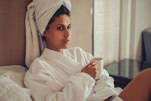 Girl in bathrobe with towel on her hair drinking coffee on the bed