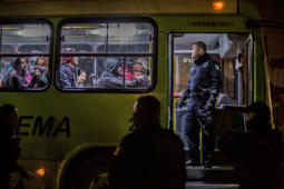 19 December 2018, Mexico, Tijuana: A policeman checks a bus to take a group of migrants to an emergency shelter in the Mexican city of Tijuana. You've been staying in front of a stadium so far. Migrants wishing to enter the USA via Mexico will in future have to wait in Mexico while their US asylum application is being processed. A corresponding agreement between the two countries was announced by the US Department of Homeland Security and the Mexican Department of State. Photo: Omar Martinez/dpa (Photo by Omar Martinez/picture alliance via Getty Images)