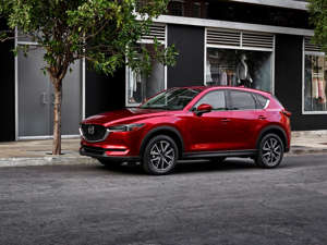 a red car parked in front of a building: 2019 Mazda CX-5