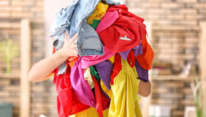 Woman holding pile of colorful clothes indoors