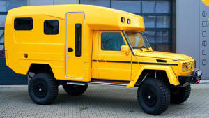 a yellow and black truck parked in a parking lot: Orangework Mercedes G-Class Camper