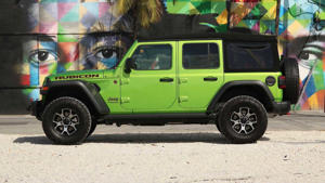 a green and yellow truck parked next to a car: 2018 Jeep Wrangler Rubicon: Review