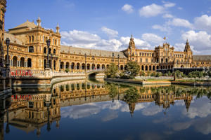 On the occasion of the Ibero-American Exposition of 1929, the magnificent Plaza de España, a symbol of the so-called regionalist architecture whose maximum exponent is the architect Aníbal González, was built in the city of Seville, among other buildings. It stands out for the successful combination of the brick seen from its structure with the tiles and varied ornaments of polychrome ceramics.  The main attractions of the square are its semicircular lake, the twin towers, the banks on which appear, through tiles, 49 provinces of Spanish provinces and its beautiful coffered ceiling.