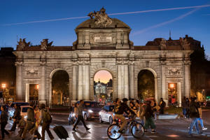 The Puerta de Alcala of Madrid at dusk with people in the streets and city lights. Nightlife in Madrid.