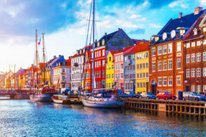 Scenic summer sunset view of Nyhavn pier with color buildings, ships, yachts and other boats in the Old Town of Copenhagen, Denmark