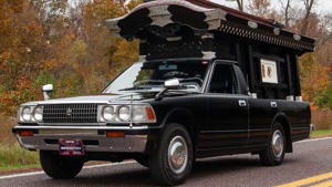 a car parked in front of a truck: Toyota Crown Hearse For Sale On eBay
