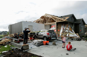 A neighbor and grand children of absent homeowners are seen in front of a weather-damaged home in the Hyda Hills neighborhood in Bellevue, Neb., Saturday, June 17, 2017. A severe weather front passed through the area the previous evening. (AP Photo/Nati Harnik)
