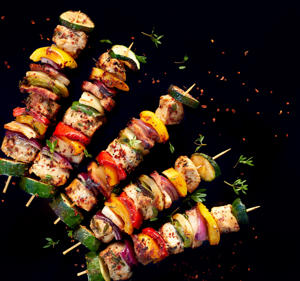 Grilled skewers of meat and vegetables on a dark background