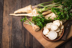 Fresh parsley root on the wooden table