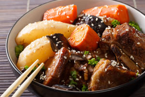 Spicy ribs stewed with mushrooms, pears and carrots close-up in a bowl. horizontal. Korean style