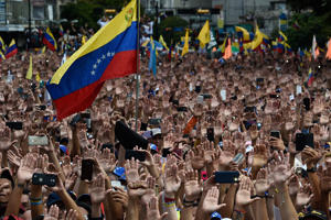 TOPSHOT - People raise their hands during a mass opposition rally against President Nicolas Maduro in which Venezuela's National Assembly head Juan Guaido (out of frame) declared himself the country's 'acting president', on the anniversary of a 1958 uprising that overthrew a military dictatorship, in Caracas on January 23, 2019. - 'I swear to formally assume the national executive powers as acting president of Venezuela to end the usurpation, (install) a transitional government and hold free elections,' said Guaido as thousands of supporters cheered. Moments earlier, the loyalist-dominated Supreme Court ordered a criminal investigation of the opposition-controlled legislature. (Photo by Federico PARRA / AFP)        (Photo credit should read FEDERICO PARRA/AFP/Getty Images)