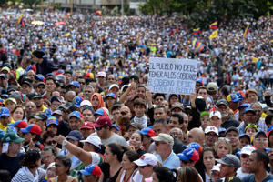 A man holds a placard reading 'The People Shouldn't Fear the Governments, But the Government Should Fear the People' as Venezuela's National Assembly head Juan Guaido (out of frame) speaks to the crowd during a mass opposition rally against leader Nicolas Maduro in which he declared himself the country's 'acting president', on the anniversary of a 1958 uprising that overthrew a military dictatorship, in Caracas on January 23, 2019. - 'I swear to formally assume the national executive powers as acting president of Venezuela to end the usurpation, (install) a transitional government and hold free elections,' said Guaido as thousands of supporters cheered. Moments earlier, the loyalist-dominated Supreme Court ordered a criminal investigation of the opposition-controlled legislature. (Photo by Federico PARRA / AFP)        (Photo credit should read FEDERICO PARRA/AFP/Getty Images)