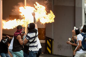 Opposition demonstrators clash with security forces in a protest against the government of President Nicolas Maduro on the anniversary of the 1958 uprising that overthrew the military dictatorship, in Caracas on January 23, 2019. - Venezuela's National Assembly head Juan Guaido declared himself the country's 'acting president' on Wednesday during a mass opposition rally against leader Nicolas Maduro. (Photo by Federico Parra / AFP)        (Photo credit should read FEDERICO PARRA/AFP/Getty Images)