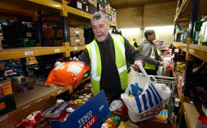 Volunteers Des Flanagan and Jamie watts (background) at the Black Country Food Bank prepare food parcels for vulnerable individuals and families at their base in Halesowen