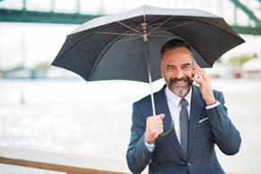 Business man on a rainy day, chatting with a colleague and holding an umbrella.