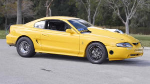 a yellow car parked on the side of a road: 7 Second Manual SN95 Cobra