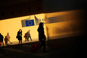 Commuters walk past the European Commission headquarters in Brussels