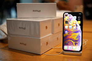 Boxes of iPhones purchased by customers are pictured next to an iPhone XS on display at the Apple Store in Singapore September 21, 2018. REUTERS/Edgar Su