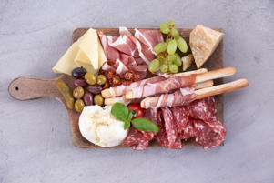 Italian antipasti wine snacks set. Grizini, cheese variety, Mediterranean olives, pickles, Prosciutto, salami white background, top view