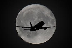 A passenger plane is seen with the moon behind as it begins its final landing approach to Heathrow Airport in London, Britain, September 25, 2018. REUTERS/Toby Melville