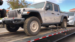 a truck is parked in front of a car: Jeep Gladiator On Trailer
