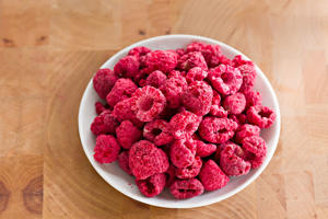 A high angle close up of a small white bowl full of crunchy & delicious freeze-dried raspberries.