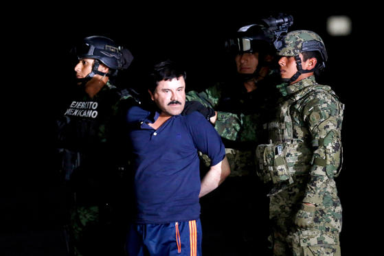 "Slide 1 of 8: Soldiers escort drug lord Joaquin ""El Chapo"" Guzman during a presentation to the media in Mexico City, Mexico January 8, 2016."