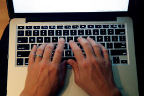FILE - This June 19, 2017, file photo shows fingers on laptop keyboard in North Andover, Mass. Americans appear to be heeding expert advice for keeping their passwords and accounts safe. A new poll by The Associated Press and the NORC Center for Public Affairs Research finds that 41 percent of Americans use unique passwords for most or all online services. (AP Photo/Elise Amendola, File)