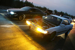 Novyy Urengoy, Russia - August 12, 2016: Motor cars Nissan Laurel and Toyota Mark II take part in the night street drag racing.