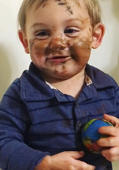 Little baby puts make-up all over his face