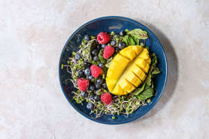 Green vegan salad with berries strawberry, blueberry, sprouts, young beetroot leaves, mango on blue plate over grey concrete background Top view, space Healthy eating. (Photo by: Natasha Breen/REDA&CO/UIG via Getty Images)