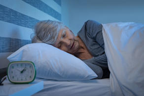 Old woman in grey hair sleeping peacefully at night time in bed. Senior woman lying on side and sleeping at home. Mature woman feeling relaxed at home while sleeping at night.