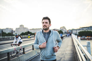 Handsome runner jogging in London, listening to music.
