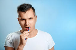 A man in a white T-shirt brushes his teeth against a blue background. The concept of oral hygiene.