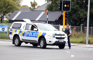 Police stand guard on a street near the Christchurch mosque which came under attack.