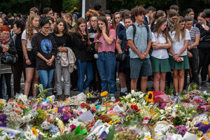 Schoolchildren and other well-wishers view flowers and tributes near Al Noor mosque on March 18, 2019 in Christchurch, New Zealand. 50 people were killed, and dozens are still injured in hospital after a gunman opened fire on two Christchurch mosques on Friday, 15 March. The accused attacker, 28-year-old Australian, Brenton Tarrant, has been charged with murder and remanded in custody until April 5. The attack is the worst mass shooting in New Zealand's history.
